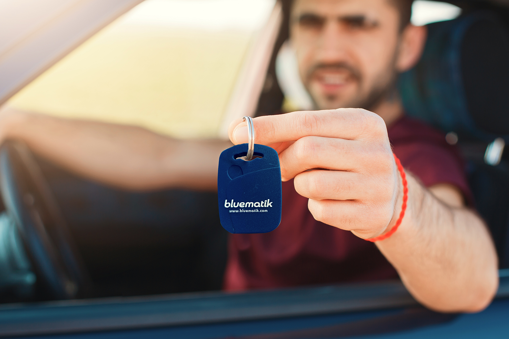 Handsome male holds car key while sits in automobile, sells his auto, travells in long journey. Man haulier drives on long distance. Focus on key. Horizontal shot. People and transportation concept
